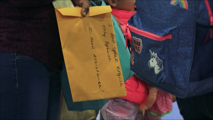 Migrants hold manila folders with a message in English asking for assistance while traveling