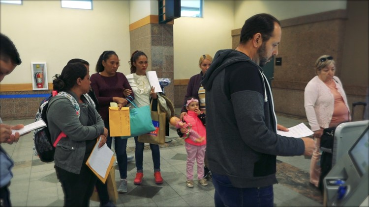 Caminos de Vida Associate Pastor Israel Cabrera helps migrant families check in at the El Paso International Airport