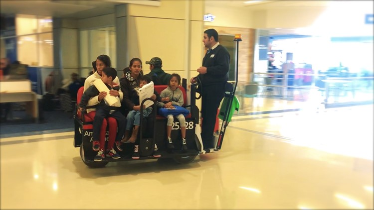Central American mothers carry their children on their laps as they are escorted to their gates at DFW airport