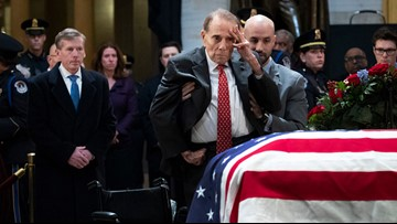 Frail Bob Dole helped from wheelchair to salute fellow hero Bush 41