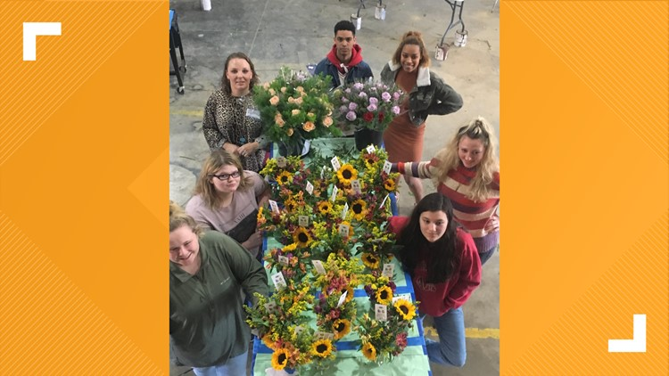 Lindale Floral Manager Shay Jacobs helps students in a floral design class put together bouquets